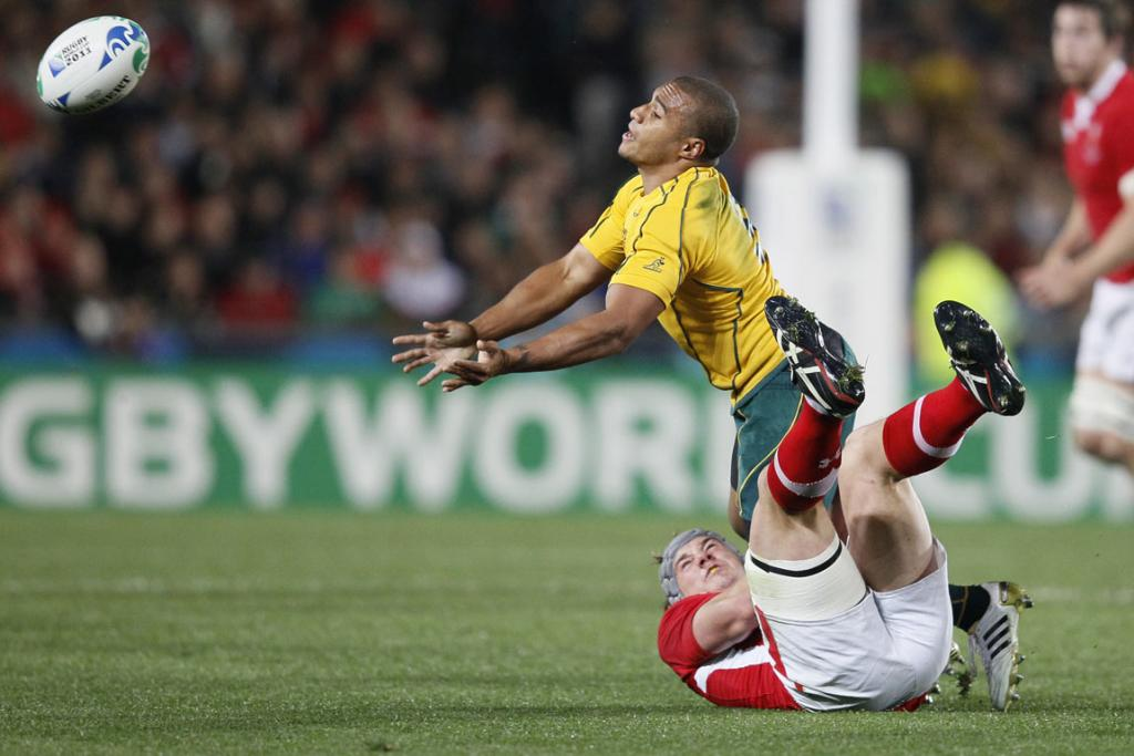 Australia halfback Will Genia passes the ball as he is tackled by Jonathan Davies of Wales.