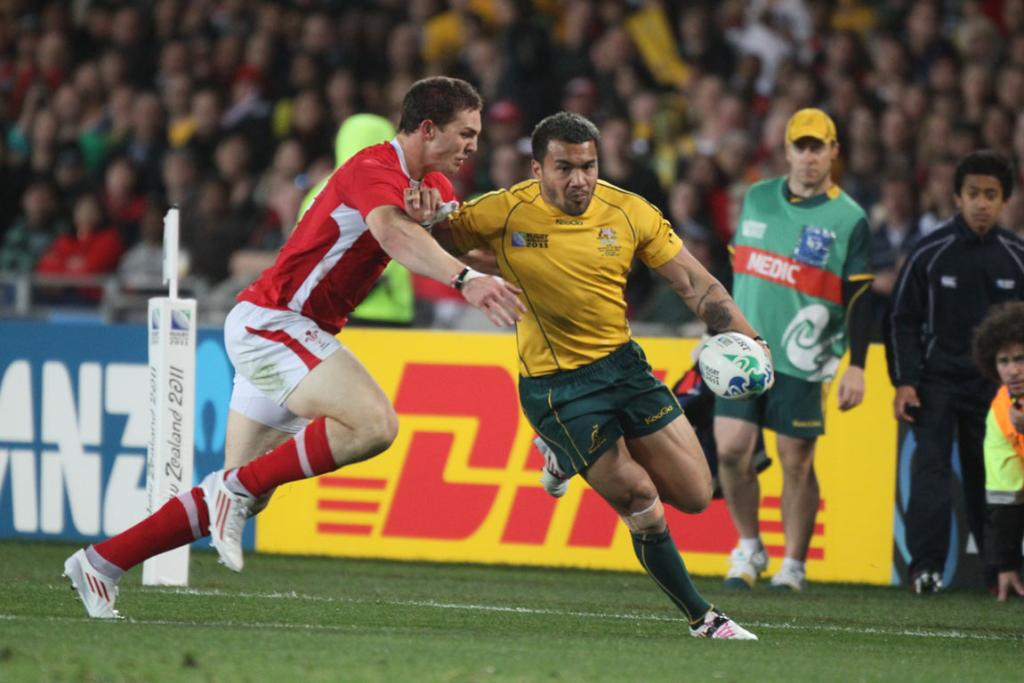 Australia left wing Digby Ioane tries to beat Wales right wing George North.