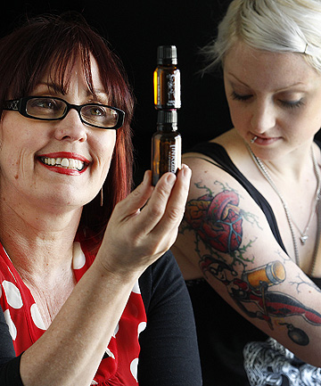 SOOTHING BALM: Gillian Parkinson, left, with her award-winning Tinkture Tattoo After Care product that tattoo aficionado Char Hillerby, right, says taps into the huge market for tattooing after-care merchandise, particularly vegan-based ones.