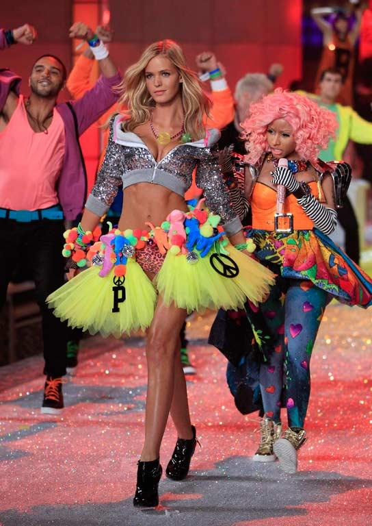 A Victoria's Secret model presents a creation as singer Nicki Minaj, right, performs.