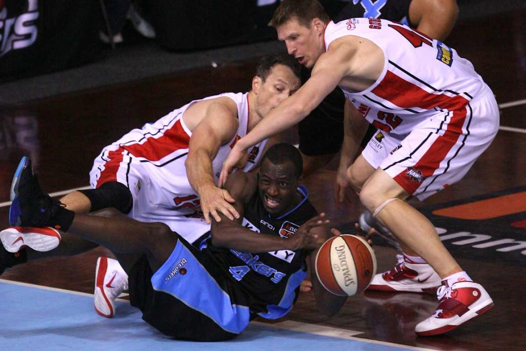 Breakers guard Cedric Jackson tussles for the ball against Glen Saville (left) and Dave Gruber of the Hawks.