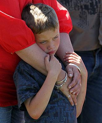 ONE YEAR ON: A boy takes comfort in his mother's arms.