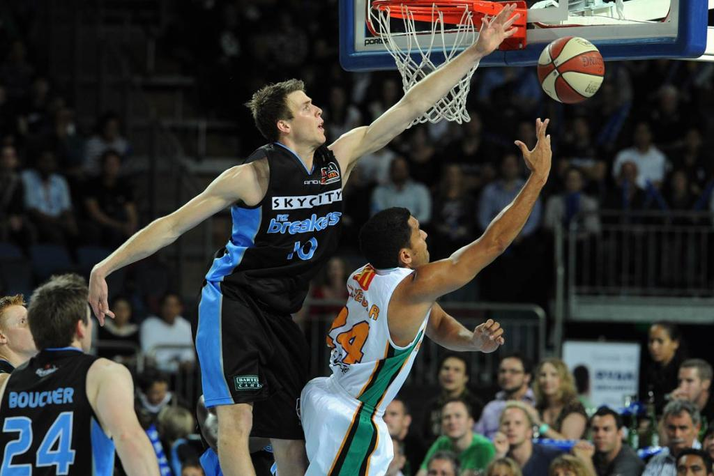 Tom Abercrombie soars over Townsville's Michael Cedar to block his shot.