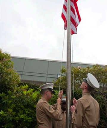 HALF-MAST: U.S. Marines lower a flag to half way to mark the 70th anniversary of the Pearl Harbor battle.