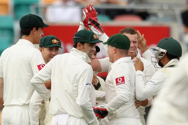 Australia's Peter Siddle is congratulated by team-mates after getting the wicket of Martin Guptill on the first day of the Second Test against New Zealand at Bellerive Oval, Hobart.