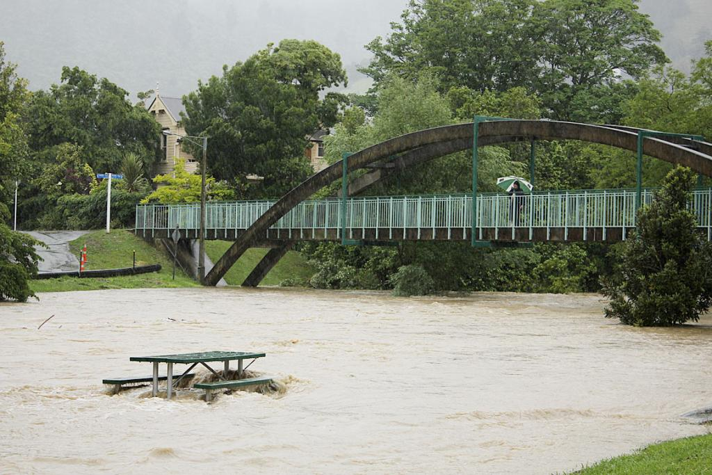 A pedestrian watches the flood waters from a bridge.