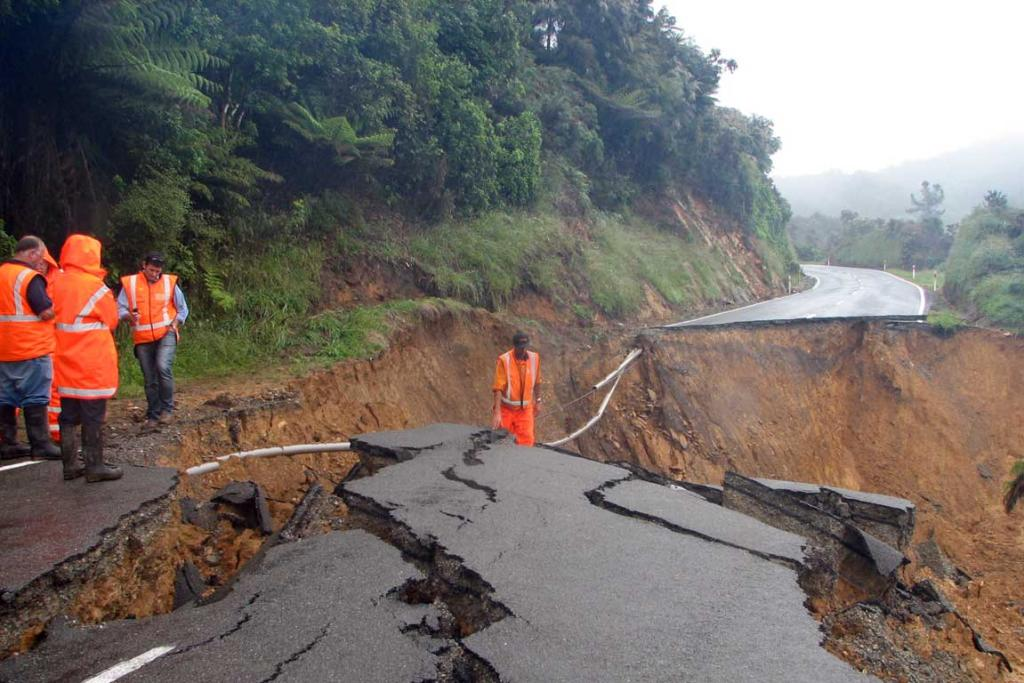 Road workers inspect the damage of a wash out on Bird's Hill, Nelson.