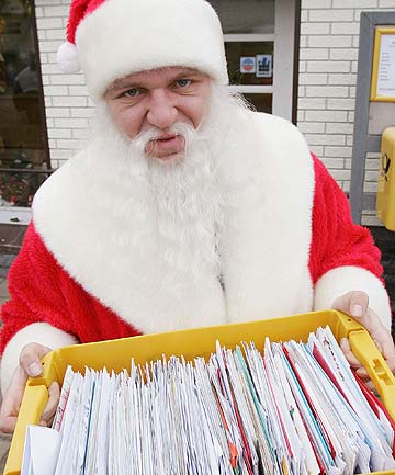 Santa holds a box of mail.