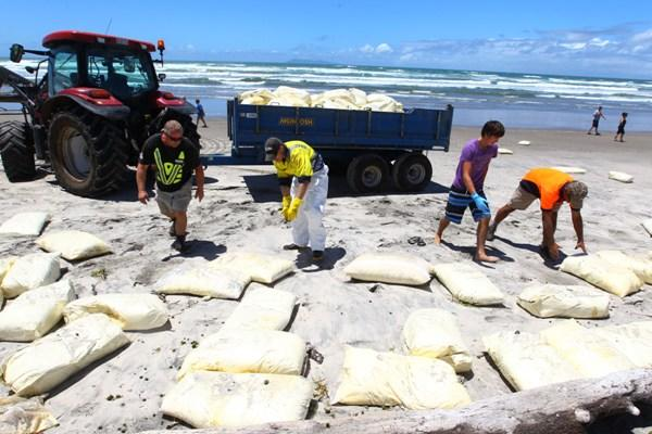NOT AGAIN: Workers clear debris from the stricken Rena that washed on to Waihi Beach yesterday.