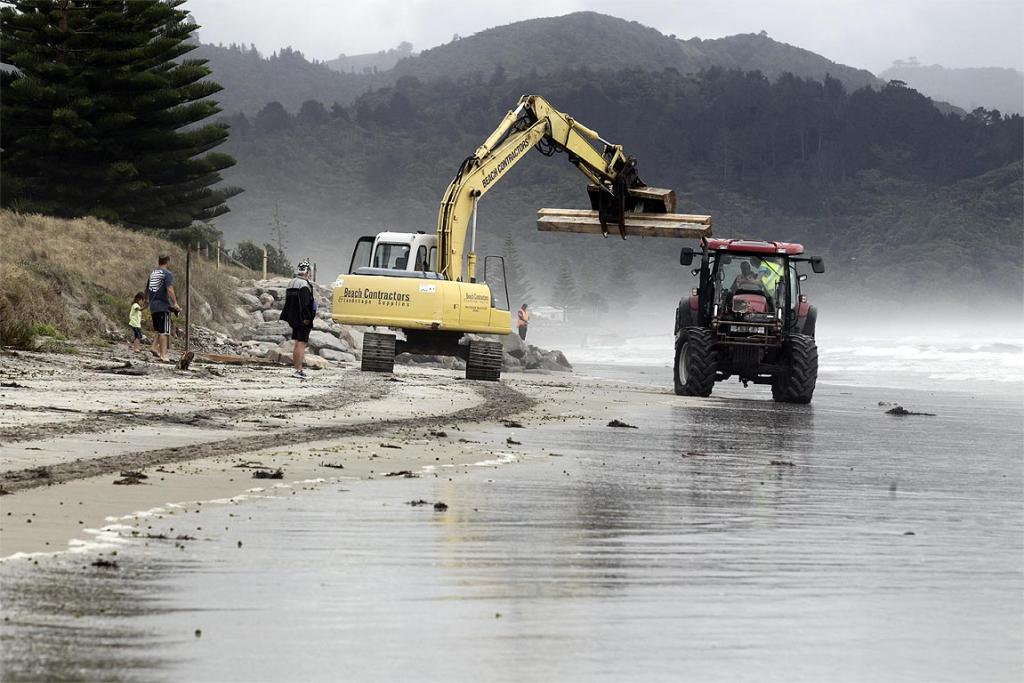 Contractors remove timber washed up on Waihi beach.