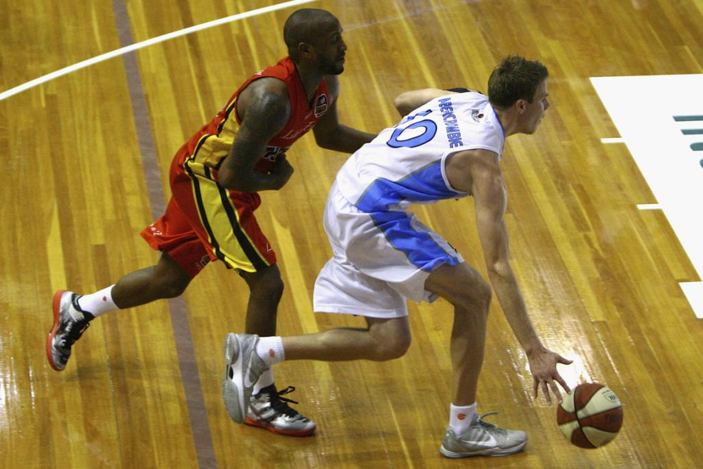 Tom Abercrombie of the Breakers drives past Ayinde Ubaka of the Melbourne Tigers.