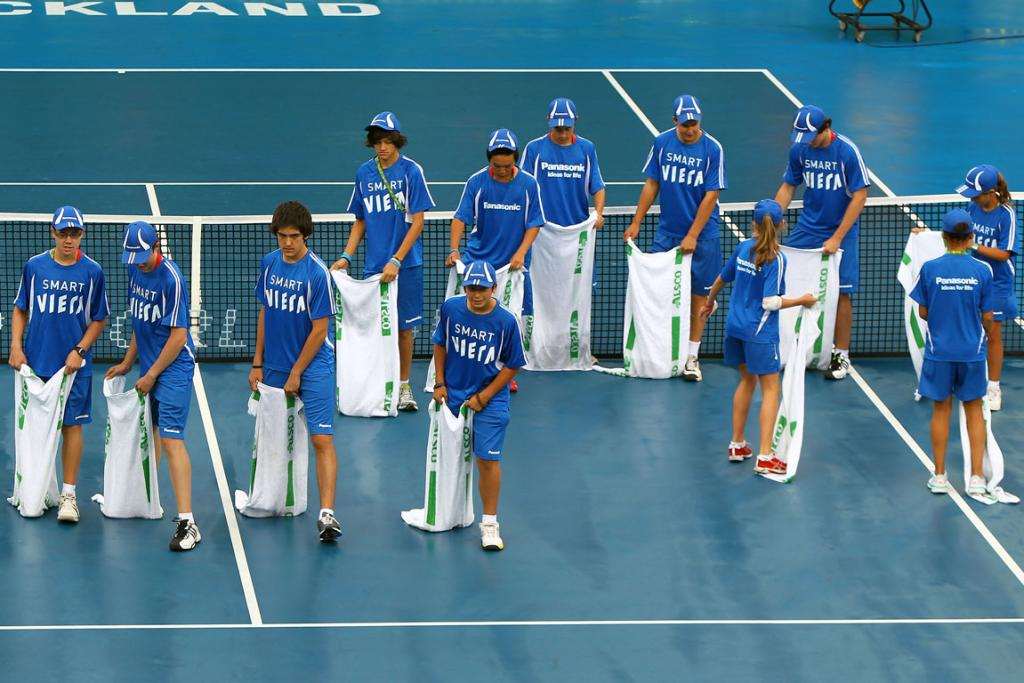 Ball kids dry the court at the Heineken Open on day 4.