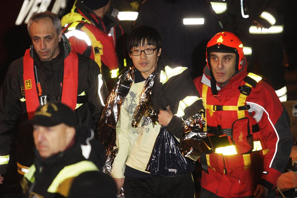 A South Korean man, centre, is helped after been rescued with his wife from Costa Concordia cruise ship.