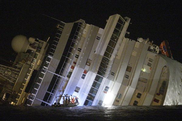 Rescuers are seen next to the Costa Concordia cruise ship that ran aground off the west coast of Italy.