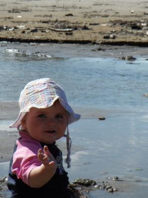 SANDY: Anita Mills snaps 11-month-old Paige Mills in the sand at Paunui Beach.