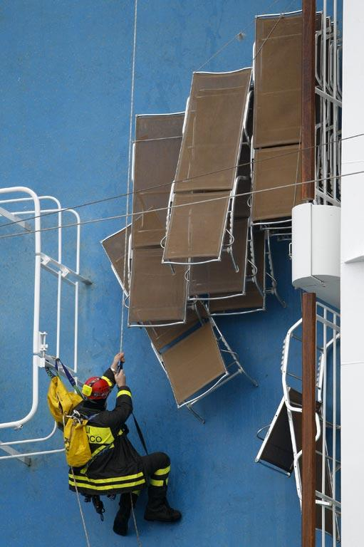 A rescue worker climbs onto the Costa Concordia cruise ship that ran aground off the west coast of Italy, at Giglio island.