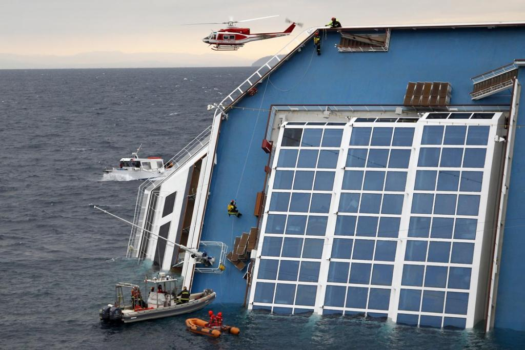 Rescue workers climb up the capsized Costa Concordia cruise ship that ran aground off the west coast of Italy at Giglio island, killing at least six people.