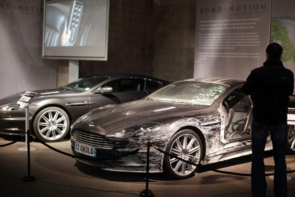 A man looks at the two Aston Martin DBS that were used in the James Bond film Quantum Of Solace at the Bond In Motion exhibition, showcasing a wide variety of vehicles used in the films.