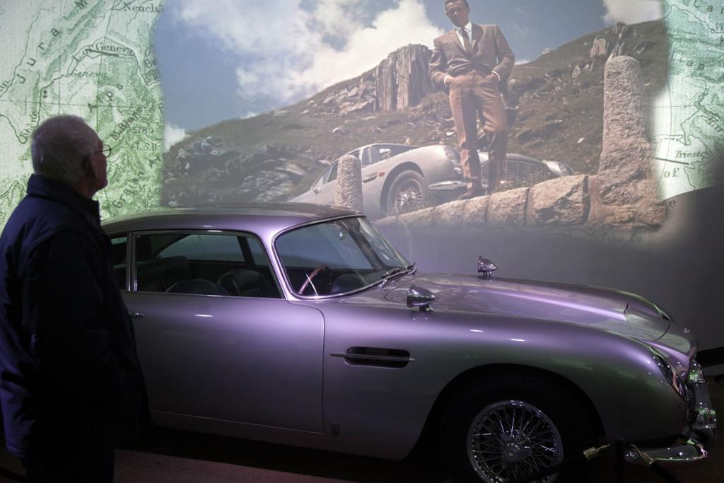 A musuem visitor looks at the Aston Martin DB5 used in the James Bond film Goldfinger in the Bond In Motion exhibition, showcasing a wide variety of vehicles used in the films.