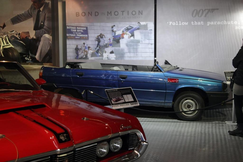 People look at cars, including a roofless Renault 11 TXE that was used in the 1985 James Bond film A View To a Kill in the Bond In Motion exhibition, showcasing a wide variety of vehicles used in the films.