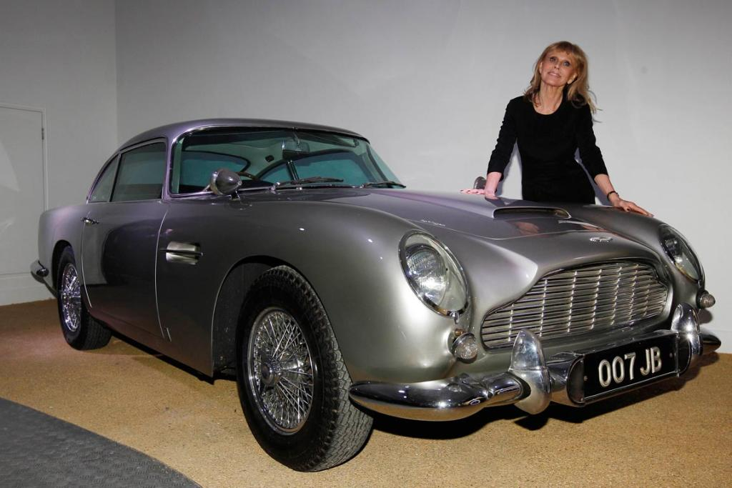 "Actress and former ""Bond Girl"", Britt Ekland, poses for photographers with an Aston Martin DB5 from the James Bond film Goldfinger at the Bond In Motion exhibition, showcasing a wide variety of vehicles used in the films."
