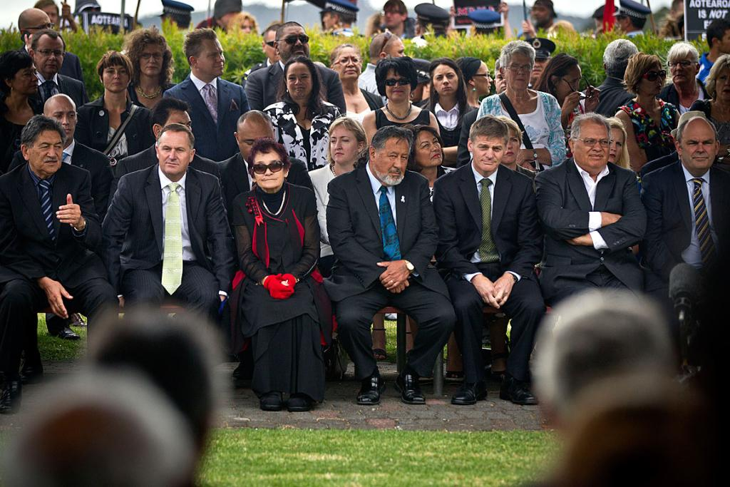 John Key sits with ministers and dignitaries.