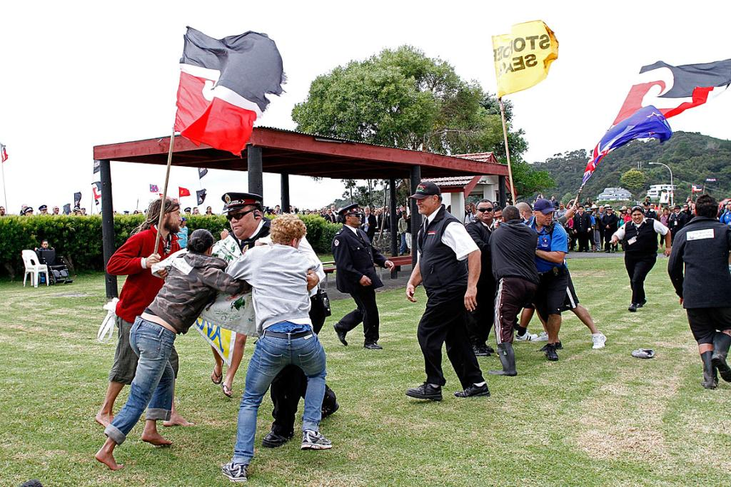 Security try to stop protesters rushing towards the prime minister.