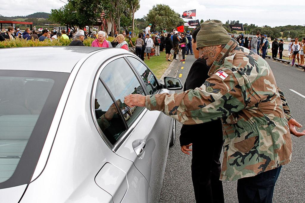 A man knocks on the window of Finance Minster Bill English's car.