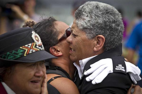 A protester embraces a Maori warden after a tense standoff at Waitangi's flagpole.
