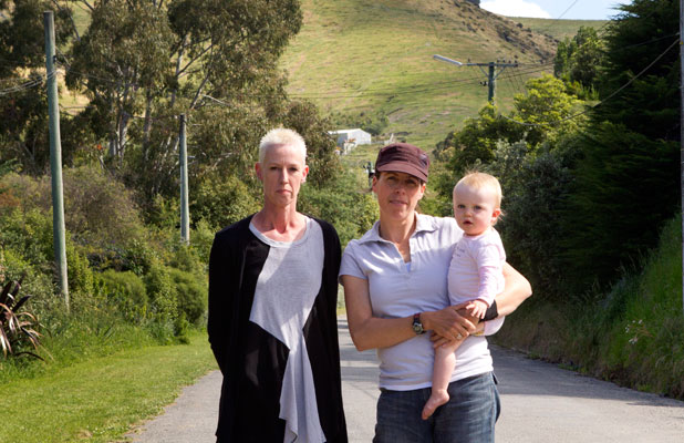 HOLDING OUT: Heather Larson, Jennifer Rochford and Rochford's daughter, Billie, in Avoca Valley Rd where Rochford's home has been red-stickered.
