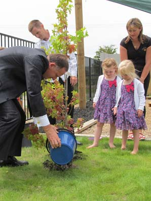 TREE PLANTING: Prime Minister John Key plants a liquid ambar with the Callander family  at the learning centre.