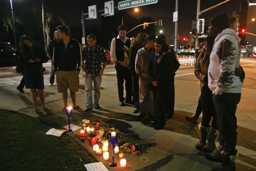People gather at a makeshift memorial on the corner of Santa Monica and Wilshire Boulevard to mourn the death of singer Whitney Houston in Beverly Hills, California.