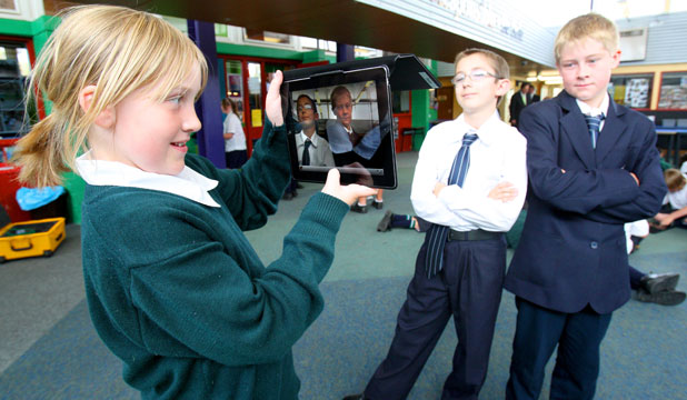 Aurora College year 7 pupil Renae Henderson uses an iPad to photograph fellow pupils Logan Murdoch and Ruben McNatty.
