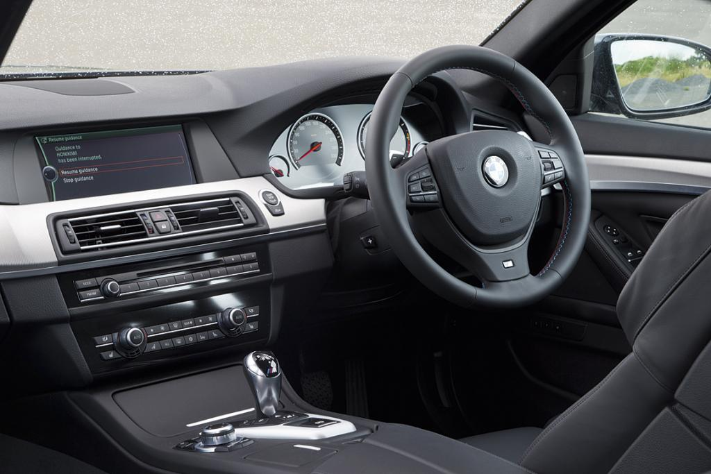 M5: Mottled alloy dash highlights and extra leather trim, plus a few M badges and special seats are visible M5 points of difference