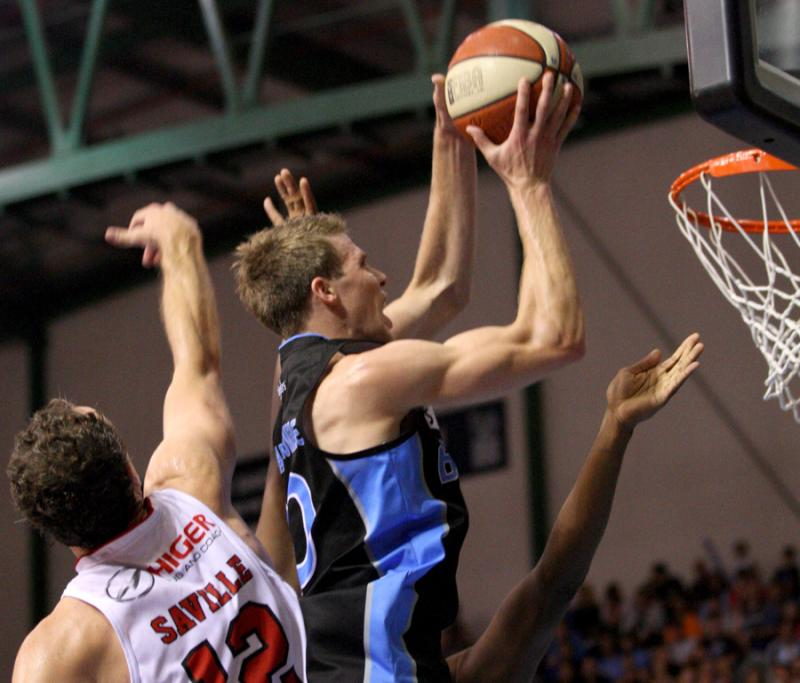 Tom Abercrombie rises above Glen Saville of the Wollongong Hawks.