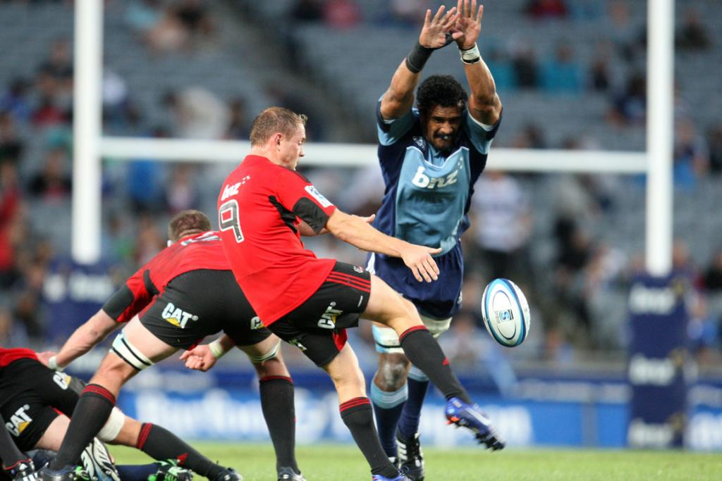 Jerome Kaino attempts to charge the kick of Crusaders halfback Andy Ellis.