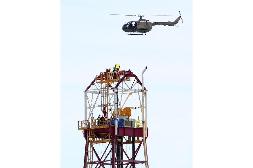 A helicopter hovers above Greenpeace activists on the Noble Discoverer.