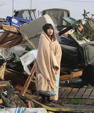 Yuko Sugimoto, wrapped in a blanket, stands in front of a pile of debris caused by the March 11, 2011 earthquake and tsunami in Ishinomaki, Miyagi Prefecture, northern Japan.