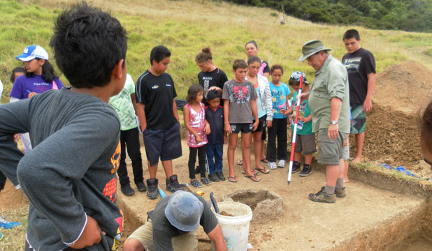 OLD SCHOOL: Te Tii School visits the dig at Oihi Mission Station.  Professor Ian Smith, centre, guided the students and whanau through the site.  Especially interesting were the remains of New Zealand's first school building, of which a fireplace, post holes and stone paths were found.  The students were also shown artefacts including slate pencils, a key, a musket ball, a clay marble and a toy cannon.  Professor Smith said it was quite likely that direct ancestors of some Te Tii School students learned to read and write on that very site.