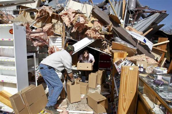 John Manley and Cristy Westfall help salvage products from the Nature's Sunshine Health Foods store after a tornado hit Branson, Missouri.