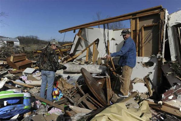 Jamie Singleton and her brother Andrew look for salvageable items from their cousin's storm destroyed apartment in Harveyville, Kansas.