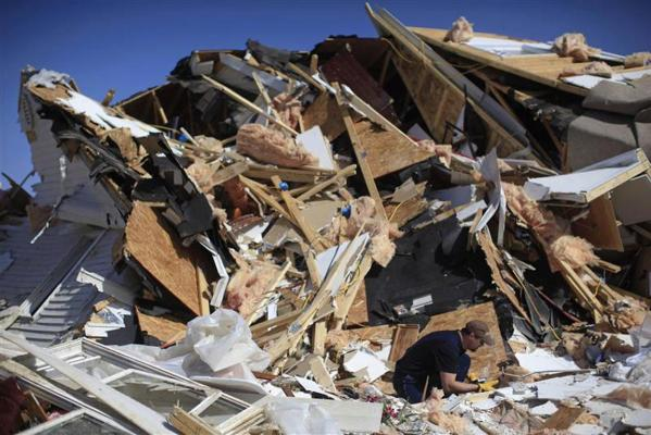 A man looks through the rubble among the destruction caused by a tornado in Harrisburg, Illinois.