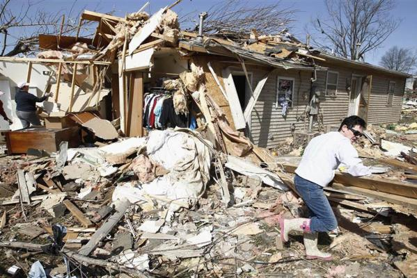 A woman helps clean up the destruction caused by a tornado in Harrisburg, Illinois.