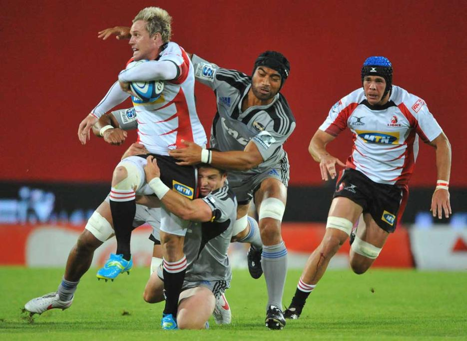 Lions forward Alwin Hollenbach is tackled by a trio of Hurricanes, including Victor Vito (right).