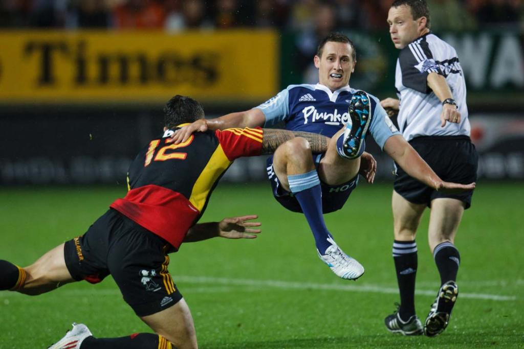 Blues first-five Michael Hobbs is hit by Sonny Bill Williams after punting the ball downfield.