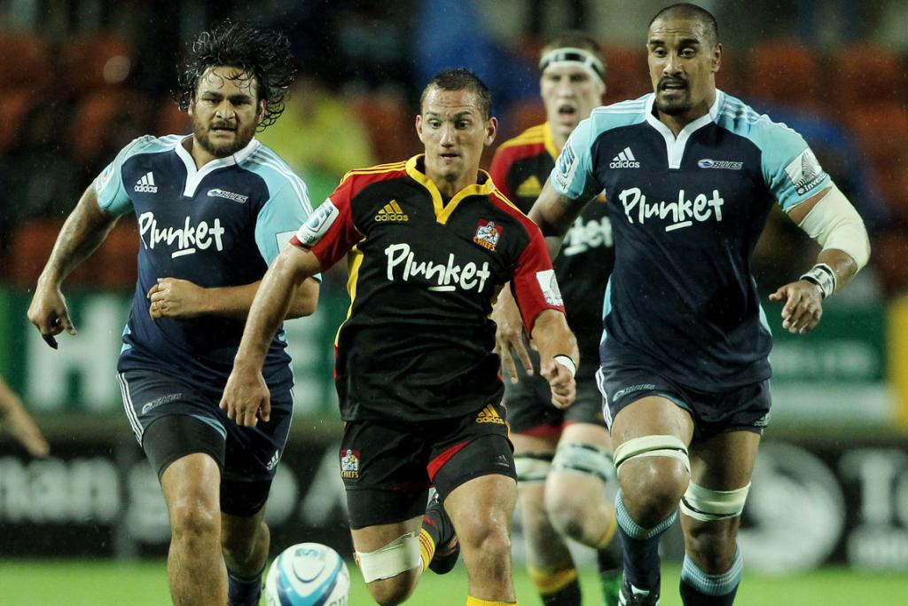 Piri Weepu and Jerome Kaino of the Blues chase down Aaron Cruden and the ball.