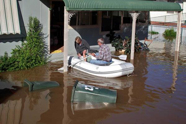 Barry Percival ferries his partner Trish Knight home in an inflatable boat down the flooded main street of Gundagai after collecting essential supplies as flood waters inundated low lying areas of the town on March 5, 2012.