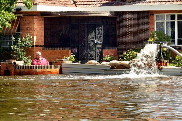 A man protects his home on March 4, 2012, in Shepparton, Victoria, with sandbags and a pump.