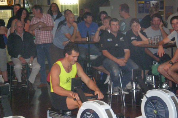 Raising the bar: Punters at Petone Working Men's Club cheer on Axel Dickinson as he gets ready for his 500m indoor rowing record attempt.