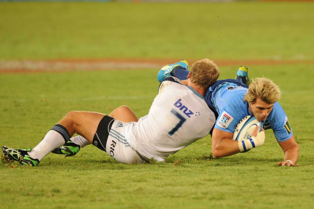 Wynand Olivier of the Bulls is tackled by Daniel Braid of the Blues.